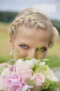 Braut mit Brautstrauss schaut durch die Pflanzen