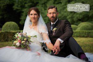 Grüntöne bearbeitet: Hochzeitspaar sitzend auf der Wiese vor Buchsbaumkugeln, Brautstrauß in mediterranen Farben (Grüntöne farblich gefiltert passend zum Brautstrauß)