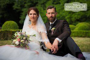 Hochzeitspaar sitzend auf der Wiese vor Buchsbaumkugeln,  Brautstrauß in mediterranen Farben (Grüntöne normal)