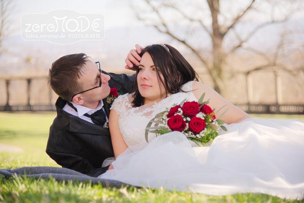 Hochzeitspaar liegt auf der Wiese in der Märzsonne