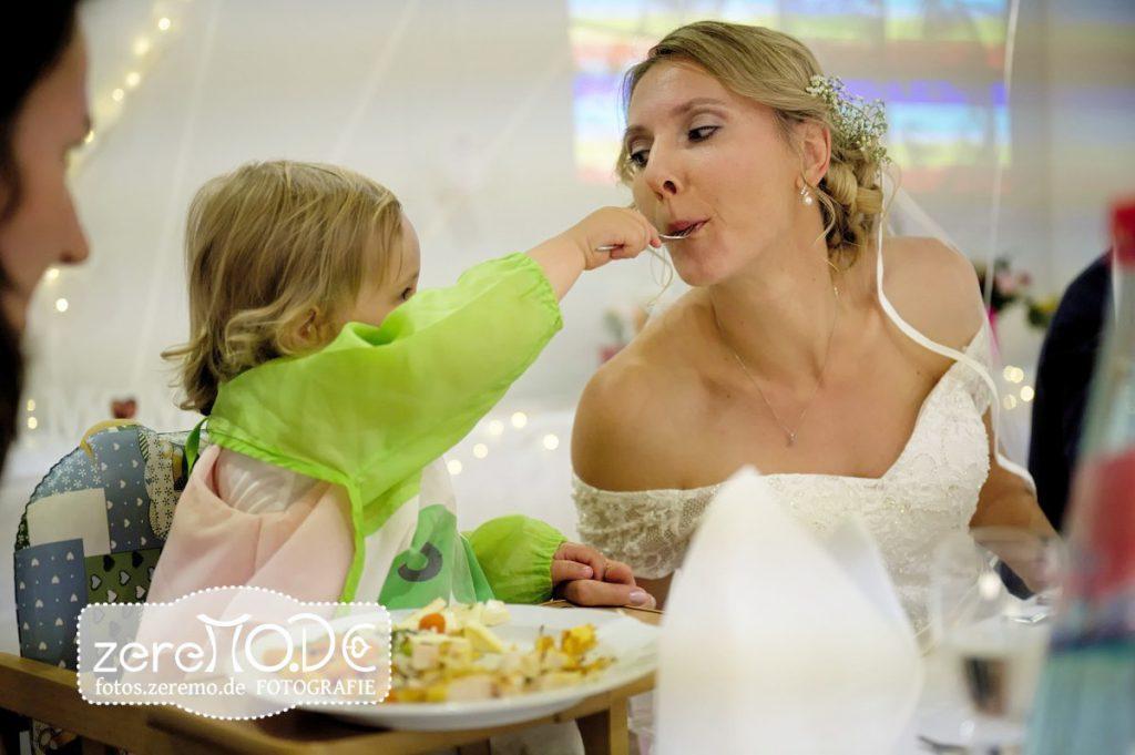 Das Blumenkind füttert die Braut beim Hochzeitsessen
