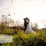 Hochzeitspaar auf einer Wiese im November im Gegenlicht, Stirn aneinandergelehnt