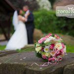 Brautstrauß auf einem Stein, Hochzeitspaar im Hintergrund