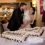 Braut und Bräutigam kämpfen darum, wer beim Anschneiden der Hochzeitstorte die Hand oben hat.