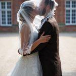 Paarshooting Hochzeitspaar, Braut und Bräutigam küssend unter dem Brautschleier