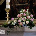 Altargesteck mit rosa und gelben Rosen und Ständer der Kerzen auf dem Altar