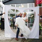 Der Bräutigam trägt die Braut durch das Lakenherz