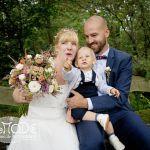 Hochzeitspaar mit kleinem Sohn auf einer bemoosten Bank, der Sohn zeigt auf etwas