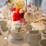 Bunte Dahlien in Gläsern auf der Hochzeitstafel