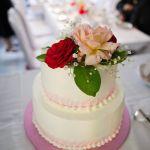 Hochzeitstorte mit roter und pfirsichfarbener Rose