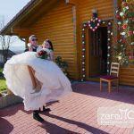 Der Bräutigam trägt die Braut über die Türschwelle