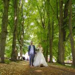 Hochzeitspaar auf einer mit Bäumen gesäumten Allee