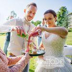 Sandzeremonie: Braut und Bräutigam schütten grünen und roten Sand aus zwei verschiedenen Gläsern in ein Glas als Symbol ihrer untrennbaren Einheit