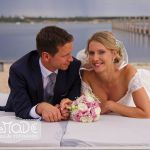 Hochzeitspaar auf einer Liege am See mit Brautstrauss, der Bräutigam sieht die Braut an